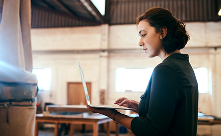 A lady in a workshop is holding and using an open laptop.