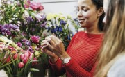 A florist examines a young flower bud with a customer