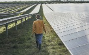 Woman walking in a field of solar panels