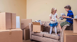 Two children on sofa surrounded by boxes