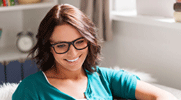 Person with glasses smiling on sofa